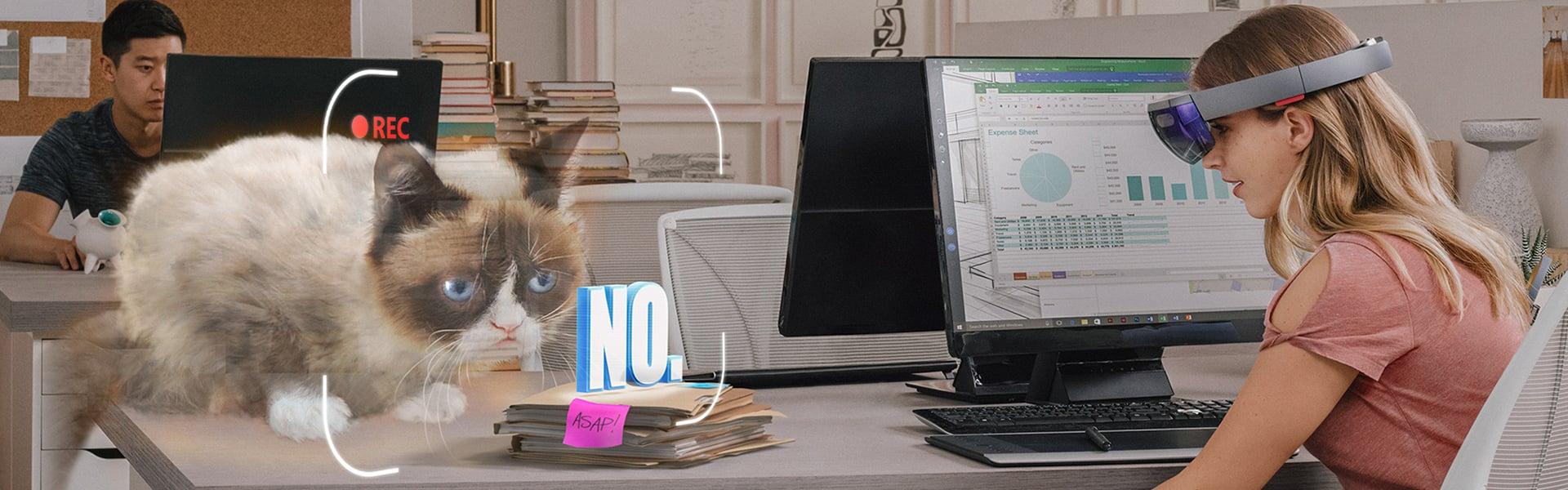 仕事机の上に座ったホログラムの Grumpy Cat を見ている、HoloLens を着けた女性