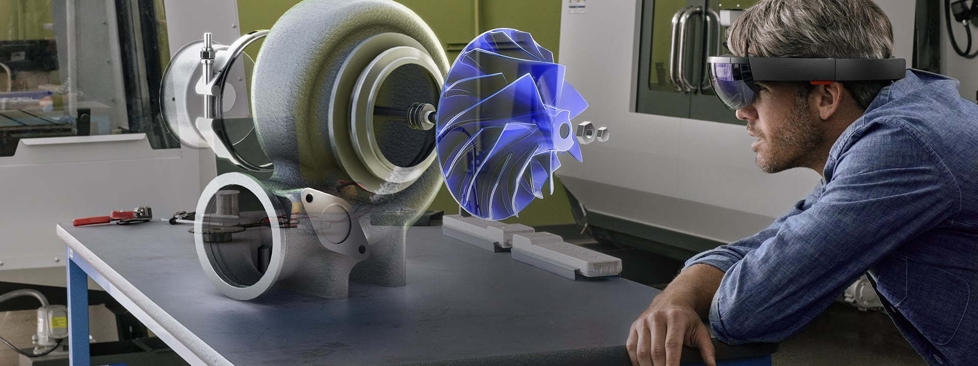 Man wearing HoloLens, leaning over a work surface, examining on a holographic engine