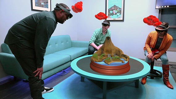 Three people have a shared mixed reality experience using HoloLens