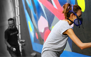 Woman wearing breathing guard spraypaints onto mural as man looks on in the background