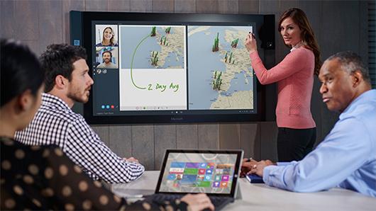 Donna che regola lo zoom con due dita sullo schermo di Microsoft Surface Hub mentre due uomini guardano