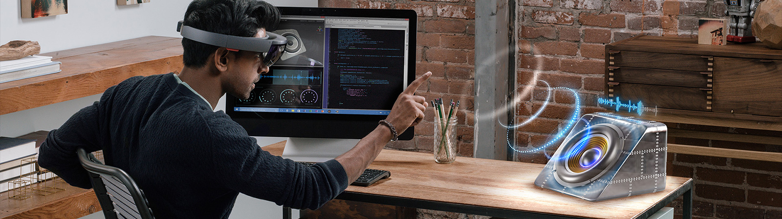 Man wearing HoloLens with code editor open on his monitor, interacting with a speaker hologram on his desk