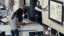 Uomo che utilizza il touch screen di Microsoft Surface Hub con uomo e donna al bancone