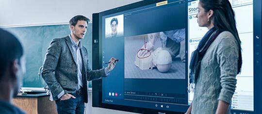 画面にいくつかのアプリが表示された Microsoft Surface Hub の前で会話する男性と女性