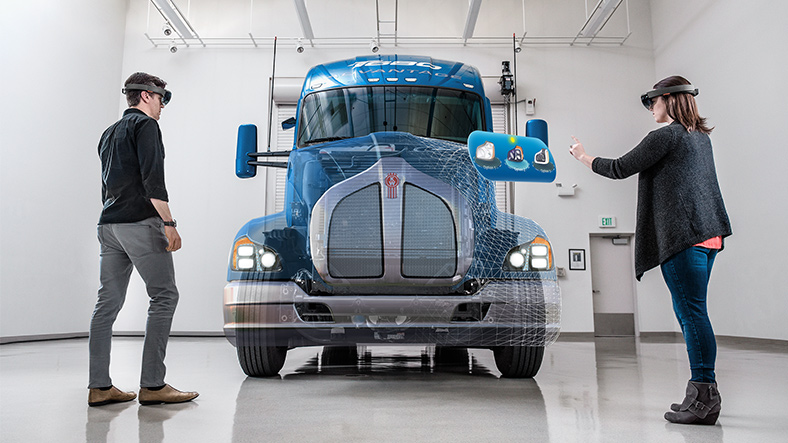 Man and woman wearing HoloLens working on a holographic truck body