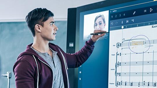 画面にアプリが表示された Microsoft Surface Hub で Surface ペンを使っている男性