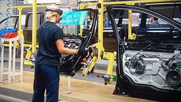A worker using HoloLens on the Volvo factory floor views holographic instructions in her field of view while using both hands to assemble a vehicle