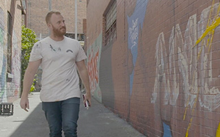 Man walks in front of a typographic mural, inspecting it
