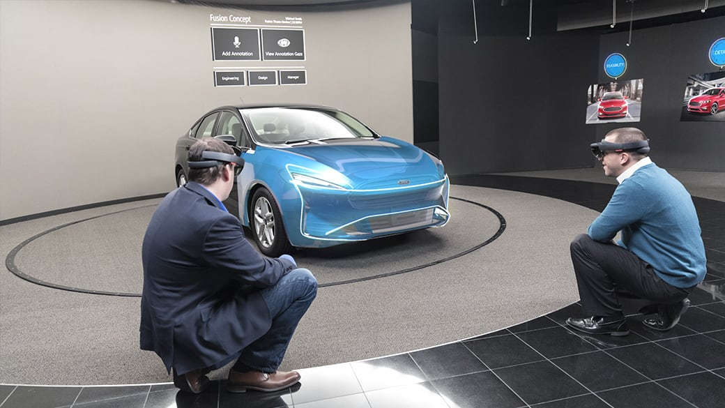 Two Ford employees using HoloLens consider a holographic design concept on a real-world car model