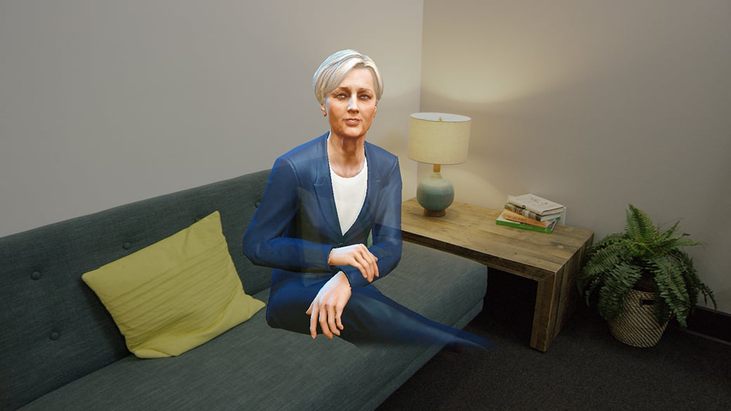A holographic woman sitting on a living room sofa facing the HoloLens wearer