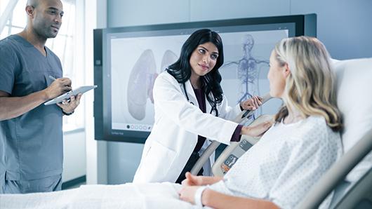 患者を安心させる医師とメモを取っている看護師、背景に Microsoft Surface Hub