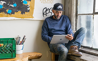Man in artist's workshop sits in corner on a windows ledge, holding a Surface tablet and touching the screen