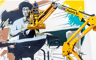 Man standing on a hydraulic crane painting a large mural