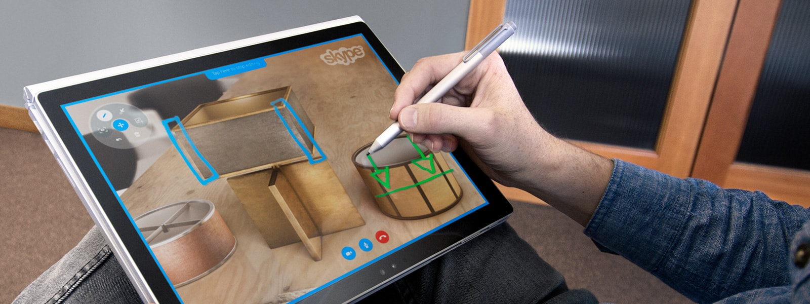 Man drawing virtual notes on top of several lampshades on a tablet screen