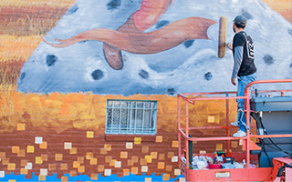 Man on hydraulic lift adding details to a colorful mural