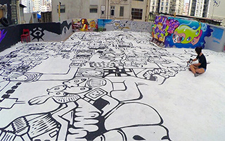 Woman sits cross-legged on a roof terrace surrounded by a massive floor mural spanning the entire floor around her