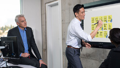 Microsoft Surface Hub で Surface ペン を使っている男性と座っている別の男性