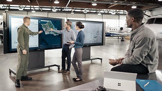 Due uomini che utilizzano il touch screen di Microsoft Surface Hub con un uomo e una donna che guardano