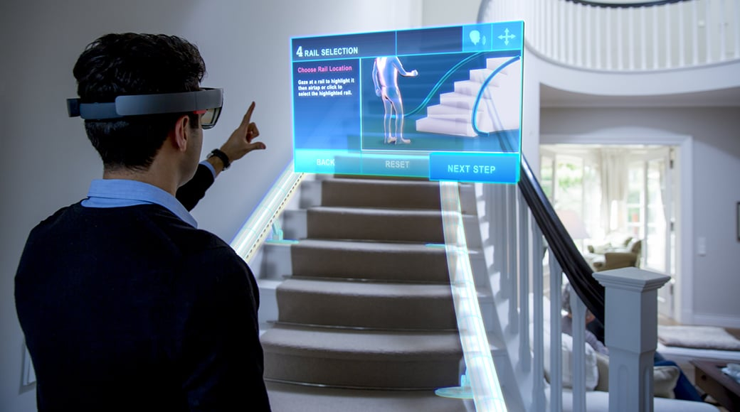 A thyssenkrupp employee uses a 3D mixed reality application on HoloLens to measure a customer's home for a custom stair lift