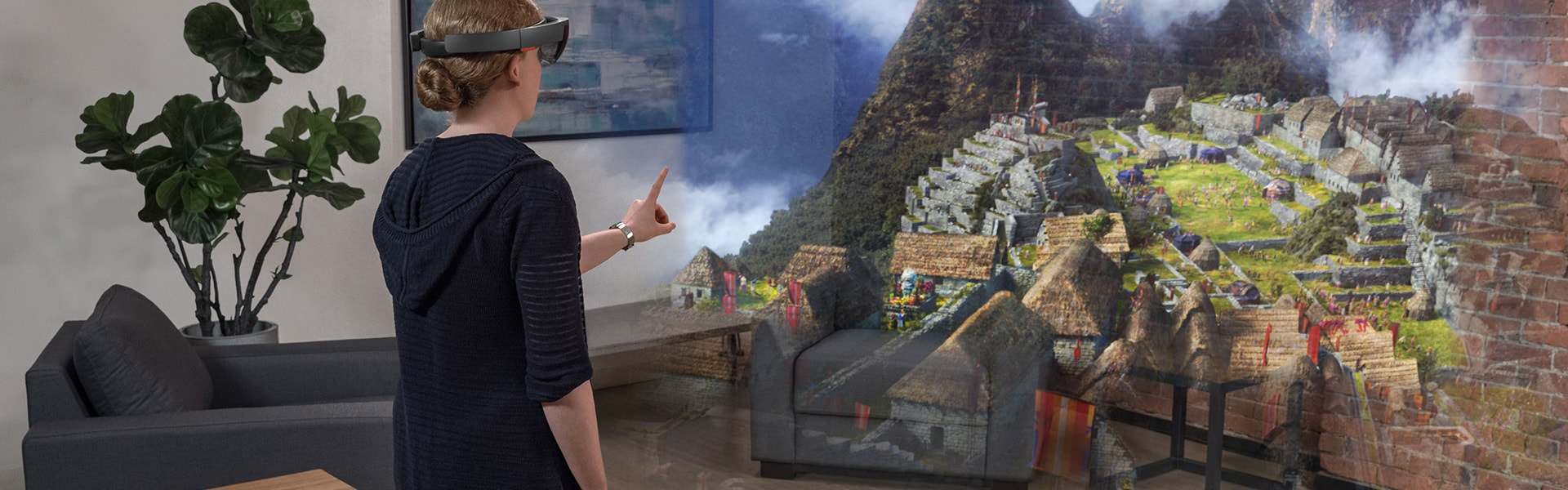 Woman wearing HoloLens, interacting with a holographic scene of an ancient village on a mountainside in her living room