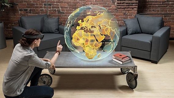 A woman uses HoloLens to view a hologram of the globe