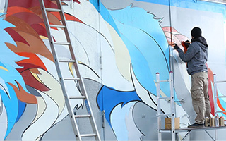 Man standing on scaffolding drawing details onto a colorful wall mural