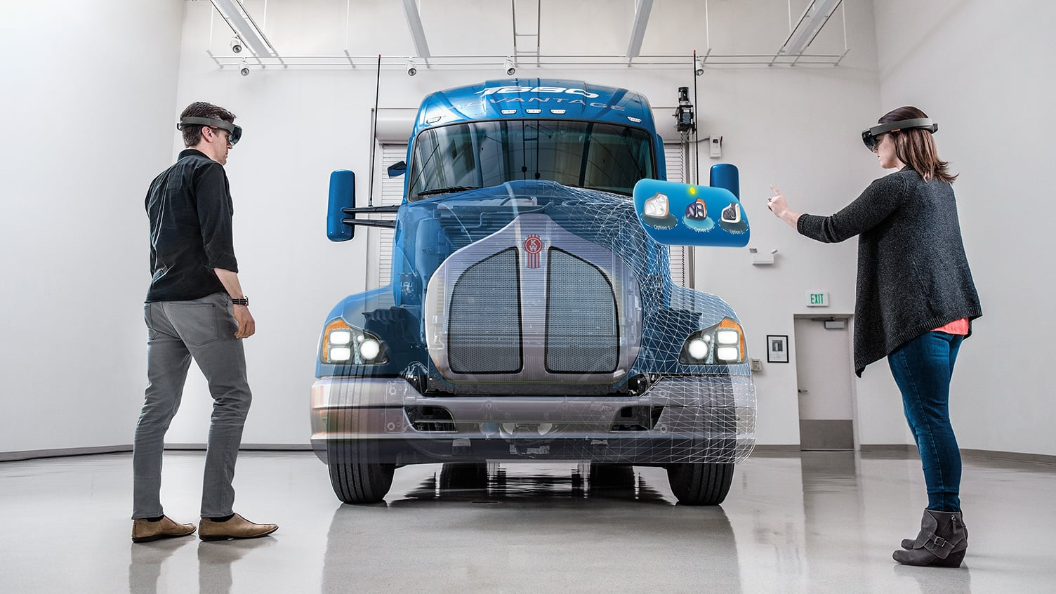 Man and woman wearing HoloLenses and working on a holographic body overlayed on a truck frame