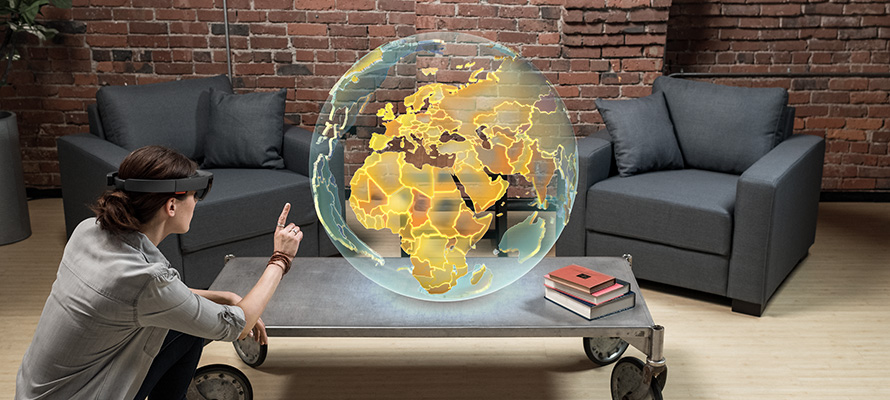 Woman wearing HoloLens interacting with a holographic globe