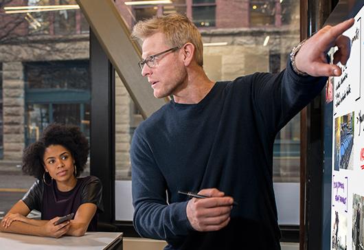 Uomo che utilizza il touch screen su Microsoft Surface Hub con due donne che guardano