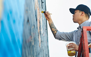 A man in baseball cap using brush to paint detail onto mural