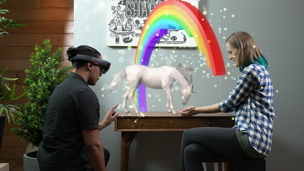 HoloLens を着けた男性が、机に座った女性の手から餌を食べるホログラムの一角獣を見ている