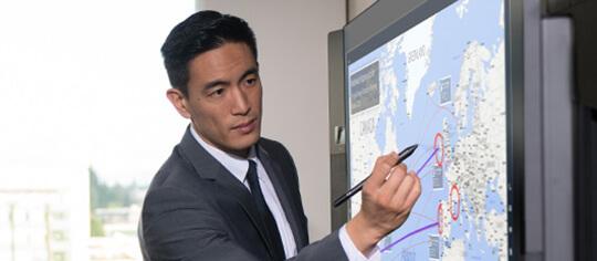 Microsoft Surface Hub で Surface ペンを使用する男性