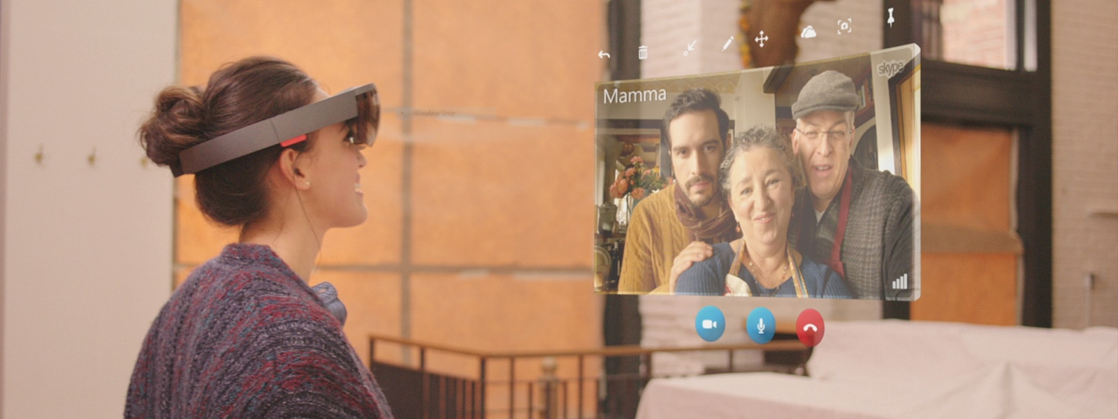 Woman wearing HoloLens speaks to family in a holographic Skype window with controls visible
