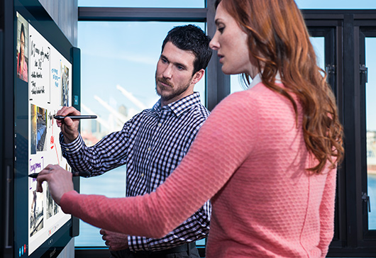 Man and woman using Surface Pen on Microsoft Surface Hub