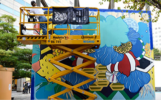 A hydraulic lift in front of a billboard with colorful mural painted onto it