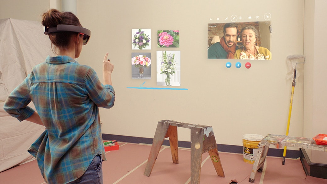 Woman wearing HoloLens speaking to relatives in a holographic Skype window while trying out hologrpahic paintings on the wall of the room she's in